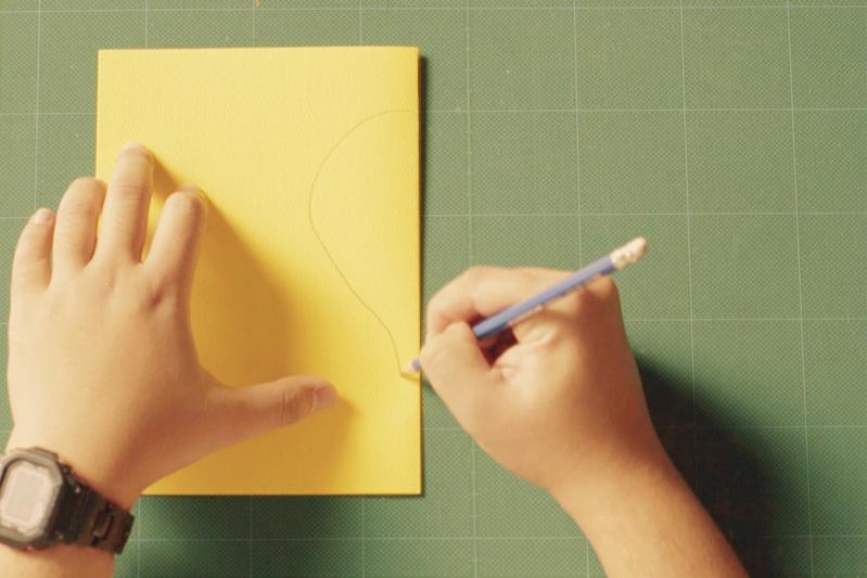 折り曲げた画用紙に絵を描く