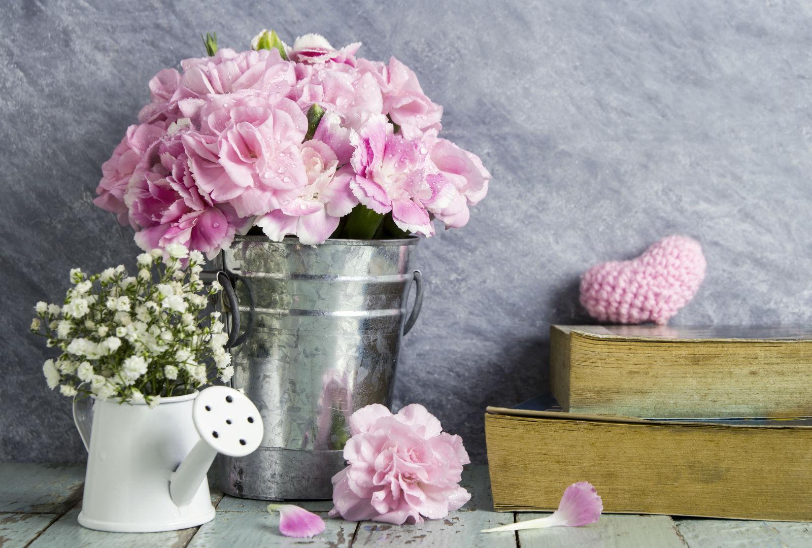 ブリキのバケツにピンクの花が生けられているイメージ。