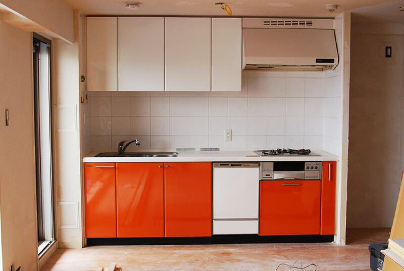キッチンBefore写真。よく見る白い人口大理石の天板に、ビビッドなオレンジの扉と白い扉。