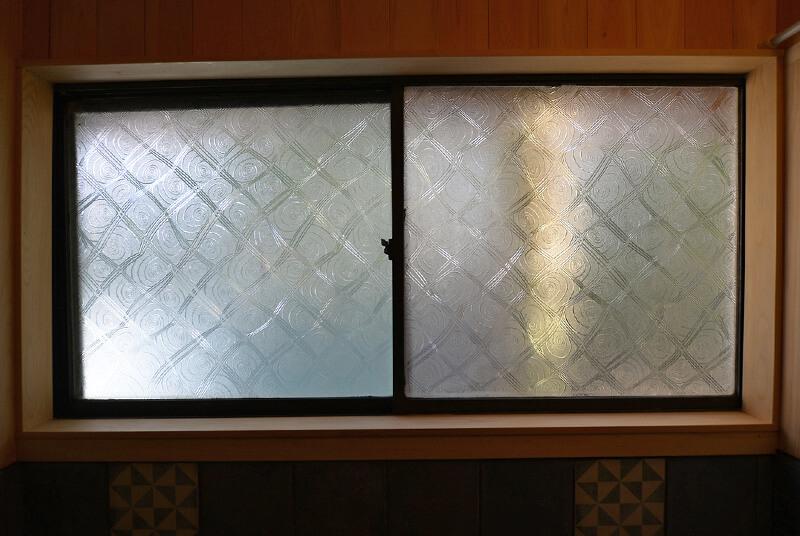 キュートな柄のお風呂の窓ガラスはそのまま生かしています。風呂釜に合わせて、まわりをアイアン塗料で塗っています