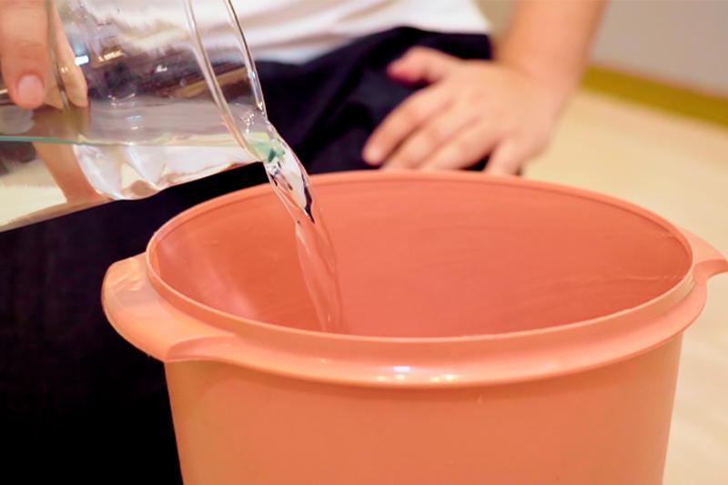 バケツにのりを混ぜる水を入れる様子