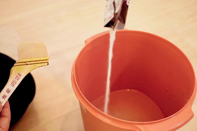 粉のりをバケツに入れ、水と混ぜる様子