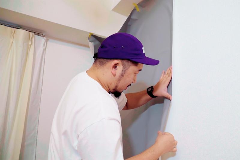 壁紙を壁に貼る様子
