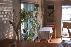 テーブルの天板の色と調和したライトグレーの壁はDIY